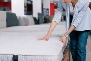 Women presses down on the surface of a mattress to test sturdiness and firmness as she goes around searching for a new mattress.